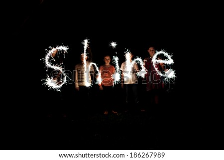 The word shine written with sparklers against a black background