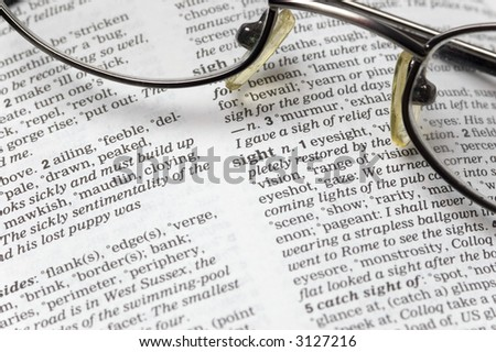 The word sight written in a thesaurus next to a pair of glasses