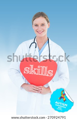 The word skills and doctor holding red heart card against blue sky - stock photo
