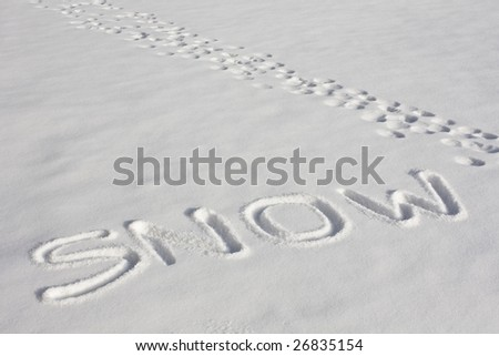"The word ""SNOW"" imprinted in a fresh snowy field beside footprints under bright sunlight"
