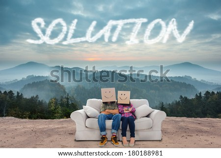 The word solution and silly employees with arms folded wearing boxes on their heads against scenic countryside with mountains - stock photo
