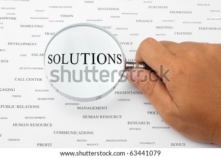The word SOLUTIONS is magnified. - stock photo