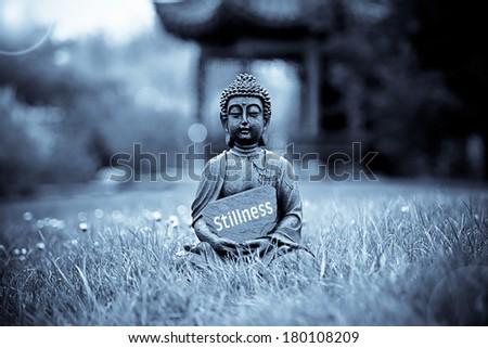 The word Stillness with Buddha Statue - stock photo