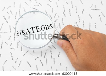 The word, STRATEGIES is magnified. - stock photo