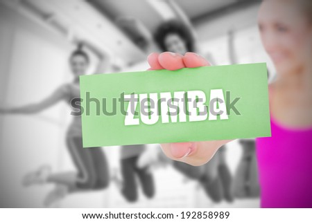 The word strength and yoga class in gym against fit blonde holding pink card - stock photo