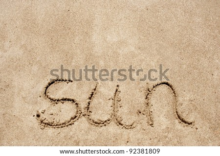 The word sun handwritten in sand on a beach as a conceptual background - stock photo