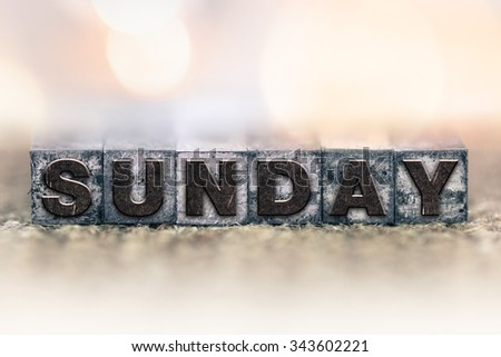 "The word ""SUNDAY"" written in vintage ink stained letterpress type."