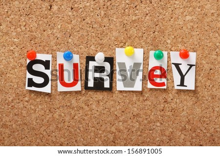 The word Survey in cut out magazine letters pinned to a cork notice board. Surveys are essential for feedback in politics and business.