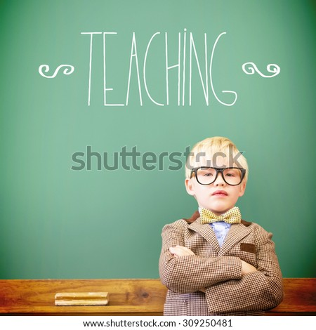 The word teaching against cute pupil dressed up as teacher in classroom - stock photo