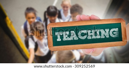 The word teaching and hand showing chalkboard against cute schoolchildren getting on school bus - stock photo