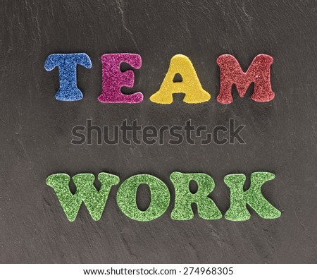 The word teamwork in colorful letters on black stone background. Conceptual image of working together, reaching goals and cooperation. - stock photo