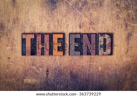 """The word """"The End"""" written in dirty vintage letterpress type on a aged wooden background. - stock photo"""