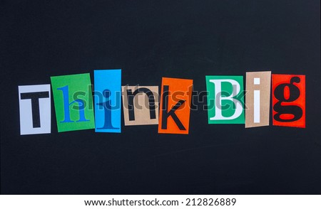 The word think big in cut out magazine letters on blackboard