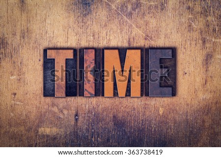 """The word """"Time"""" written in dirty vintage letterpress type on a aged wooden background. - stock photo"""