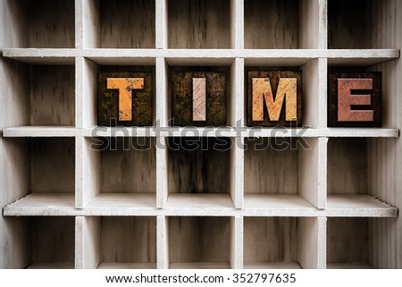 """The word """"TIME"""" written in vintage ink stained wooden letterpress type in a partitioned printer's drawer. - stock photo"""