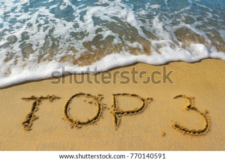 "The word ""top 3"" is written on the golden sand of the beach by the sea. The three  best beaches, tours or ways to relax in the south."