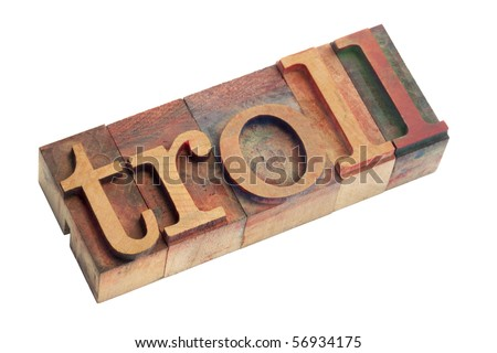the word troll (a creature from Nordic mythology or someone who posts inflammatory or off-topic messages on internet) - vintage wooden letterpress type blocks, stained by color ink, isolated on white - stock photo
