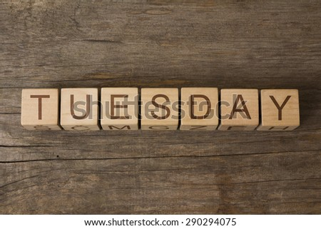 The word TUESDAY on a wooden background - stock photo