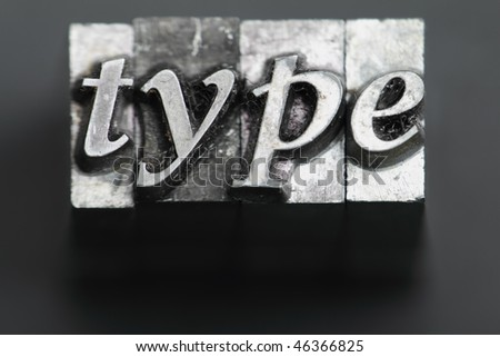 the word type in letterpress type on black background. - stock photo