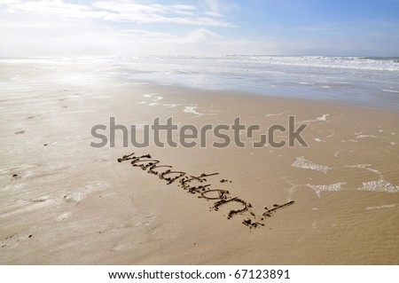 The word vacation, written in the sand on a sunny beach - stock photo