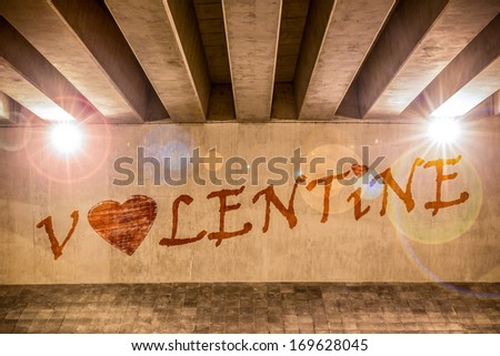 The word valentine with heart painted as graffiti on the support column of an overpass - stock photo
