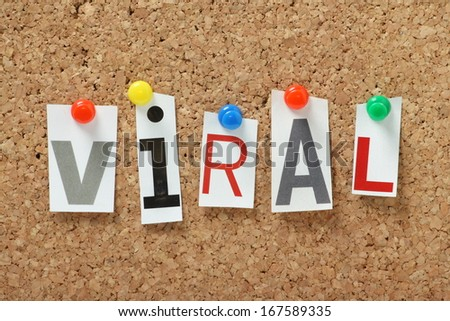 The word Viral in magazine letters pinned to a cork notice board. Viral is often used to describe an image,video or product that is widely circulated on the internet. - stock photo
