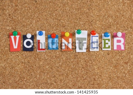 The word Volunteer in cut out magazine letters pinned to a cork notice board - stock photo