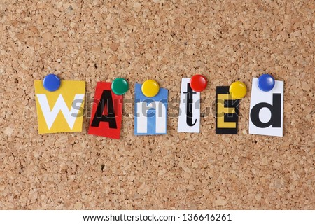 The word Wanted in cut out magazine letters pinned to a cork notice board - stock photo