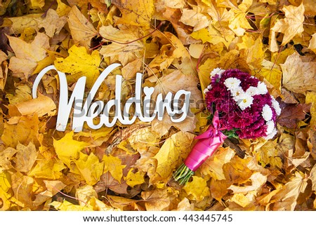 the word wedding from a tree on the yellow leaves and the bride's bouquet