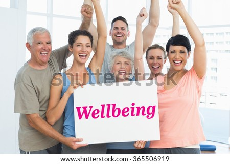 The word wellbeing and portrait of happy fit people holding blank board against grey wall - stock photo