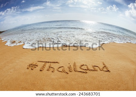 "The word with hashtag ""Thailand"" in the sand against the sea - stock photo"