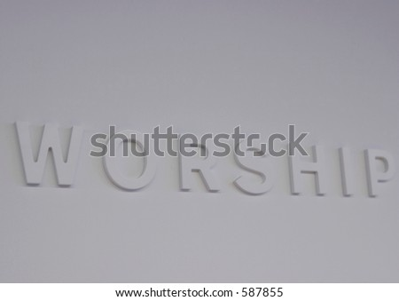 "The word ""worship"" embossed on a white wall, partially blurred"