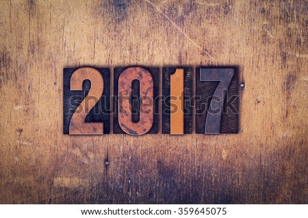 "The word ""2017"" written in dirty vintage letterpress type on a aged wooden background. - stock photo"