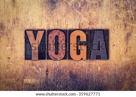 """The word """"Yoga"""" written in dirty vintage letterpress type on a aged wooden background. - stock photo"""