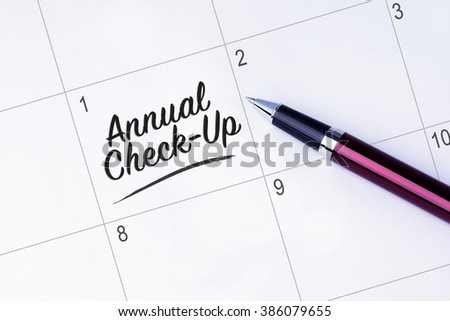 The words Annual Check-Up written on a calendar planner to remind you an important appointment with a pen on isolated white background.  - stock photo