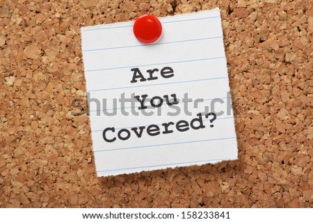 The words Are You Covered? typed on a scrap of lined paper and pinned to a cork notice board. Asking the question, are you insured for your car, travel, home or other liability. - stock photo