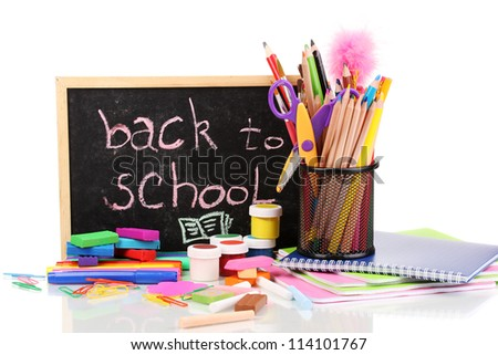The words 'Back to School' written in chalk on the small school desk with various school supplies close-up isolated on white