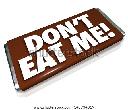 The words Don't Eat Me on a chocolate candy bar wrapper telling you this is unhealthy junk food that you should not consume if you want to lose weight and fat - stock photo