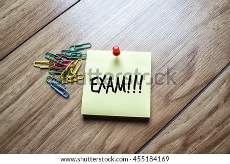 The words Exam written on a sticky note  - stock photo