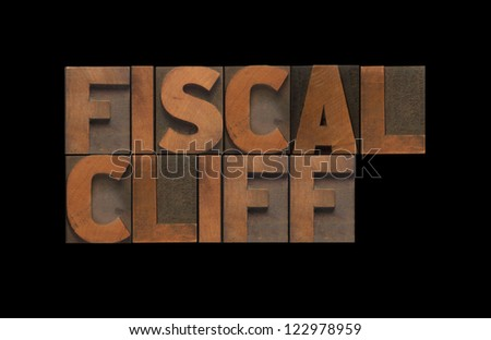 the words 'fiscal cliff' isolated on black - stock photo