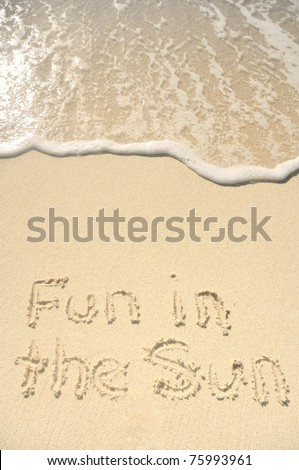 The Words Fun in the Sun Written in the Sand on a Beach - stock photo