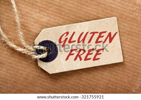 The words Gluten Free in red text on a paper price label or luggage tag with string and brown wrapping paper - stock photo
