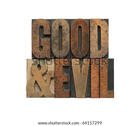 the words good and evil in old wood type - stock photo