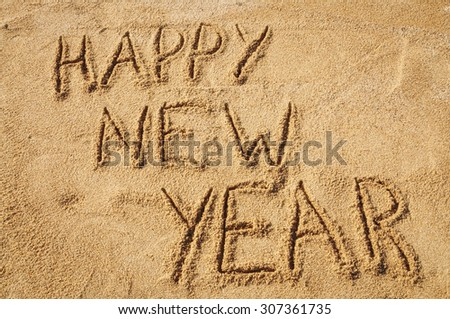 The words Happy New Year written in the sand on the beach - stock photo