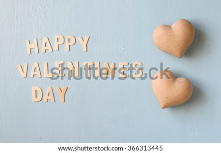 "The words ""happy valentines day"" made with block wooden letters next to couple of hearts on light blue wooden background  - stock photo"