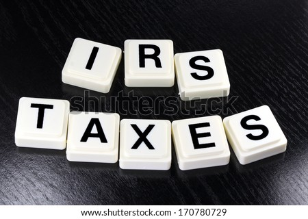 The words IRS taxes spelled out with white tiles on black background - A term used for business in finance and stock market trading - stock photo