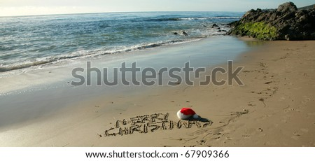 """the words """"Merry Christmas"""" written in wet sand with a """"Santa Hat"""" on a secluded beach in """"southern california"""" with the tide of the pacific ocean and blue sky in the background - stock photo"""
