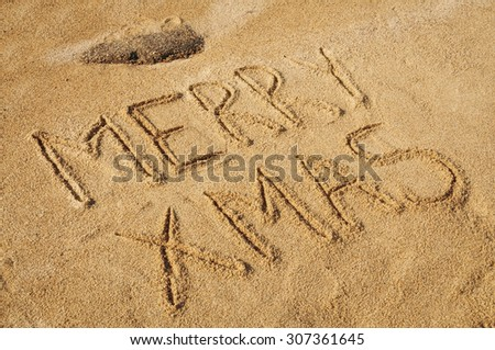 The words Merry Xmas written in the sand on the beach - stock photo