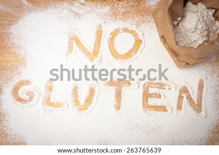 the words NO GLUTEN written on gluten free flour, overhead view - stock photo