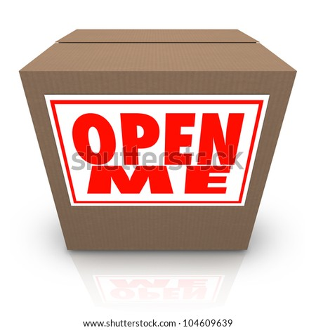 The words Open Me on a label affixed to a closed cardboard box, inviting you to open it up and see the mystery contents inside - stock photo